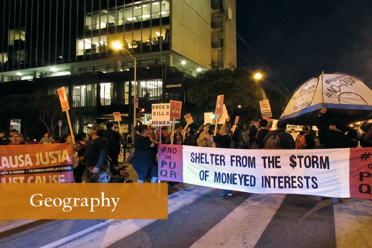 Protesters on the streets at night holding signs against gentrification efforts