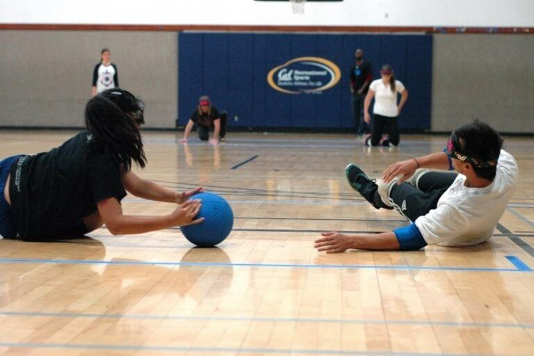 several players on the floor of a gym playing goal ball