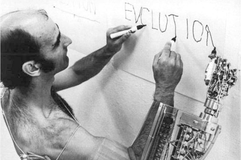 "Black and white image of a man writing ""Evolution"" using both hands on a piece of paper on a wall using both hands, man is able to write with right hand due to assistive technology"